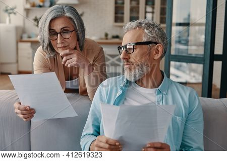 Busy Senior Couple In Casual Clothing Taking Care Of Their Finances While Bonding Together At Home
