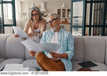 Modern Senior Couple In Casual Clothing Taking Care Of Their Finances While Bonding Together At Home