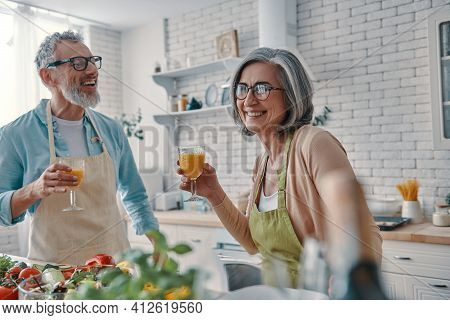 Carefree Senior Couple In Aprons Toasting Each Other With Orange Juice And Preparing Healthy Dinner