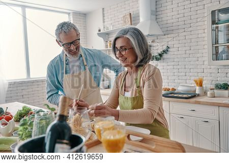 Active Senior Couple In Aprons Preparing Healthy Dinner And Smiling While Spending Time At Home