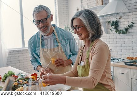 Cheerful Senior Couple In Aprons Preparing Healthy Dinner And Smiling While Spending Time At Home