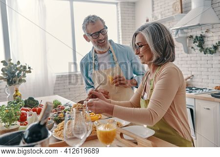 Positive Senior Couple In Aprons Preparing Healthy Dinner And Smiling While Spending Time At Home