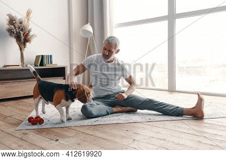 Happy Senior Man In Sport Clothing Exercising At Home Near His Dog
