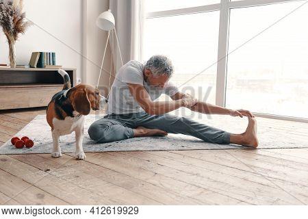 Modern Senior Man In Sport Clothing Exercising At Home Near His Dog