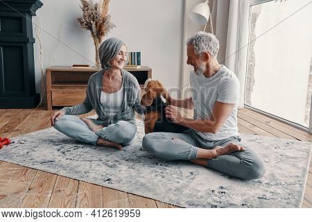 Active Senior Couple In Sports Clothing Exercising And Smiling While Spending Time At Home