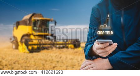 Intelligent Agriculture Concept With Growing Crop Yield. Farmer Or Agrarian With Smart Phone Looking