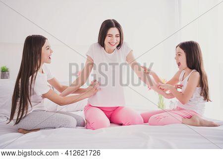 Photo Of Pretty Funky Three Siblings Nightwear Sitting Bed Smiling Tickling Older Sister Indoors Ins