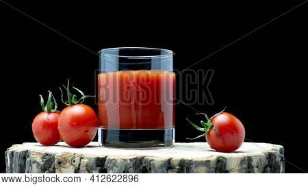 Tomato Juice In A Glass With Fresh Tomatoes On A Wooden Board On A Black Background. Natural Tomato