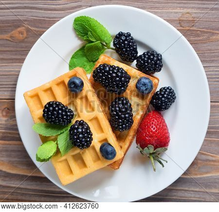Homemade Belgian waffles served with fresh berries over wooden background, close up, top view.