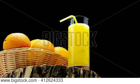 Orange Juice In A Glass With A Straw On A Black Background. Fresh Orange In A Straw Basket On A Blac