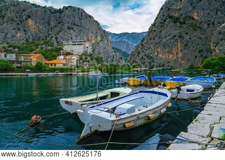Colorful Fishing And Tourist Boats On The Cetina River In Omis Resort. Anchored Colorful Boats And H