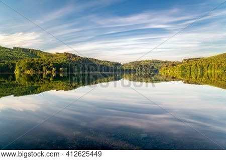 Long Exposure At The Lake With Colorful Trees And Moving Clouds. Soothing Landscape Photo For Backgr