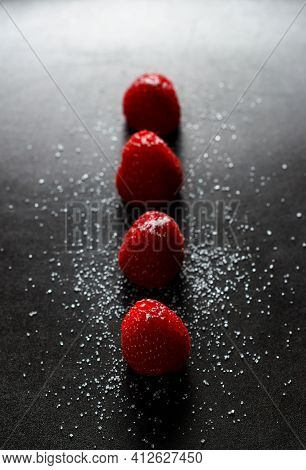Red Raspberries In A Row With Sugar On Top On A Black Griddle. Backlighting. Vertical Image.