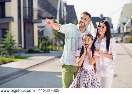 Photo Of Happy Cheerful Excited Smiling Family Outside Dad Point Finger Copyspace Mom And Child Girl