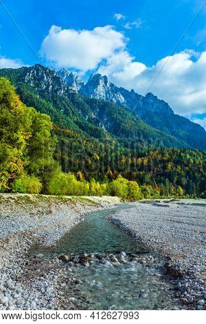 Travel to Eastern Julian Alps, fabulous Slovenia. The famous Triglav Park. The shores of Lake Jasne. Great Pysnitsa Stream. The mountains are overgrown with dense mixed forest