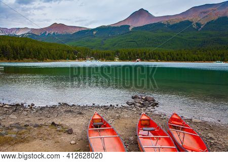 Maligne Lake in Jasper, located in the Canadian Rockies. The lake is surrounded by mountain peaks. Autumn travel to Canada. Red boats - canoes are dried on the shore of the lake