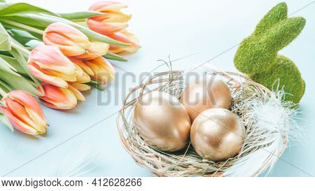Easter Symbol. Golden Eggs In Basket With Spring Tulips, White Feathers On Pastel Blue Background In