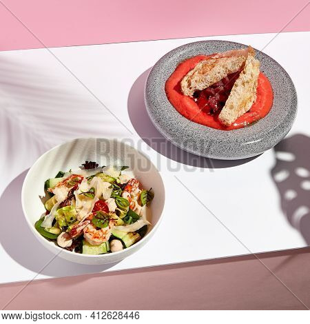 Seafood salad bowl with shrimp and vegetables. Tuna salad with bread and red espuma . Salad bowl on white table with pink wall. Sunlight with harsh shadow of green tropic leaf