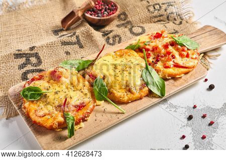 Mini pizza board on rustic white table. Pizza with cheese and tomatoes garnish with basil leaf. Small food concept
