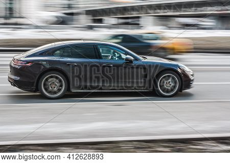 Moscow , Russia - March 3, 2021: Porsche Panamera Fast Moving On City Street. Side View Of Luxury Bl