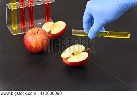 A Red Apple And Laboratory Glass With Yellow Liquid. How The Fruit Is Colored.