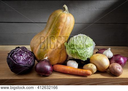 Still Life: On A Wooden Shelf In The Basement Are Pumpkins, Carrots, Red Cabbage And White Cabbage.
