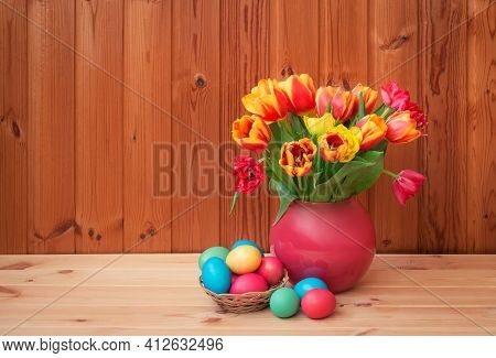 Easter Concept. Colorful Tulips In Vase  And Easter Eggs In Wicker Basket On Wooden Table. View With