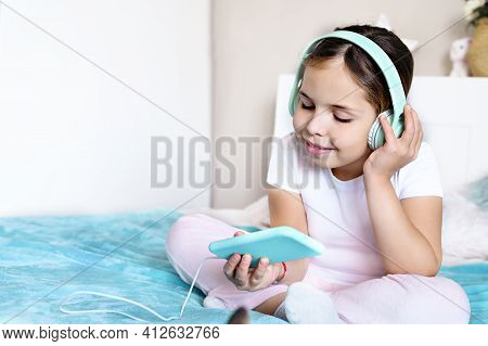 Child With Headphones Playing A Computer Game On The Phone. A Little Girl Lies On The Bed With And A