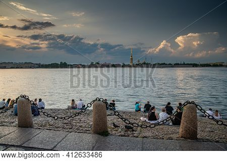 Russia, St.petersburg, 09 June 2020: People Sit On The River Bank Neva And Observe A Sunset On The R