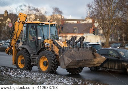 Riga, March 05, 2021: Industrial Tractor. Huge Yellow Tractor  Heavy Machine Service Car. Blurred Ba