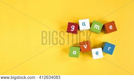Words Game Over Made From Colored Wooden Blocks. Painted Cubes With Letters On Yellow Background. Th