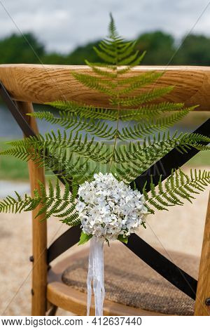 Wooden Chair For Guests Decorated With Fern Branch, Flowers, Ribbons In Rustic Style . Wedding Cerem