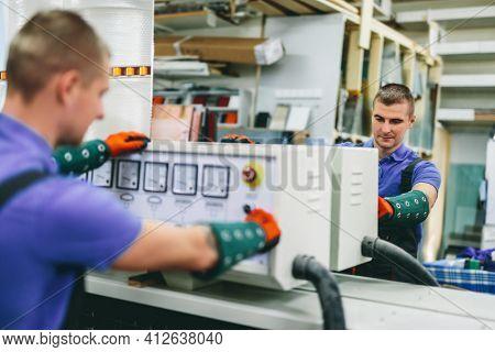 Glazier worker operates mirror glass cutting machine in workshop. Industry