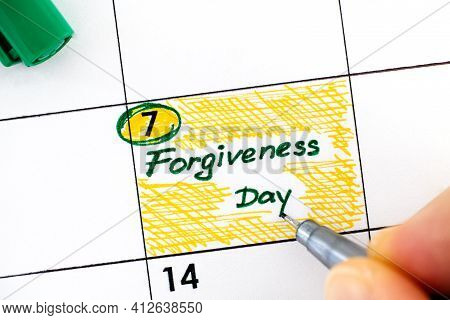 Woman Fingers With Pen Writing Reminder Forgiveness Day In Calendar. July 07.