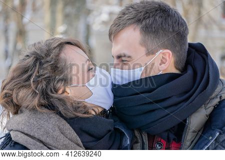 Couple Kissing Wearing Face Masks Outdoors. Man And Woman Kiss Through Facial Masks Outdoor. Lovely