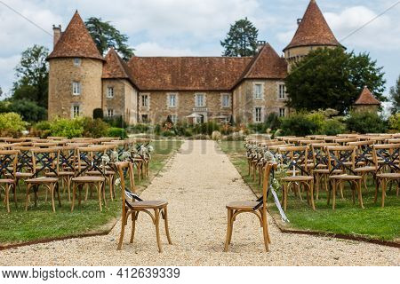 Wedding Ceremony On The Background Of Old Castle. Rows Of Wooden Chairs For Guests