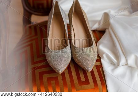 Expensive Branded Bridal Shiny Silver Shoes Standing On Chic Chair. Bride Wedding Accessories