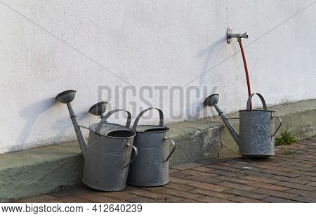 The Photo Shows Several Galvanized Watering Cans On A House Wall
