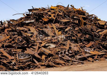 The Photo Shows A Large, Rusty Pile Of Scrap Metal In The Sun