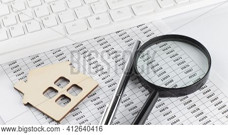 Model Wooden House And Keyboard. Image For Property Real Estate Investment Concept On Chart Backgrou