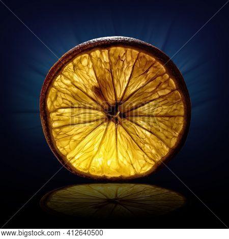 Creative Image Of A Slice Of Orange View On Backlight On Dark Blue Background