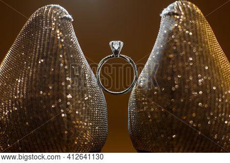 Elegant Wedding Diamond Ring Standing Between Shiny Women Wooden Heels Shoes.