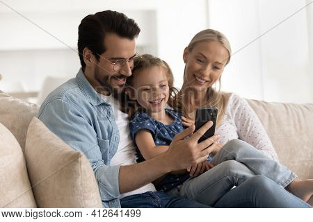 Happy Young Family With Kid Use Cellphone At Home