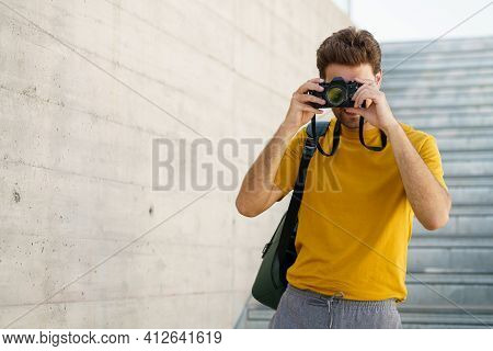 Millennial Man Taking Photographs With A Slr Camera
