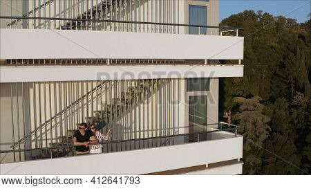 A Young Couple On The Balcony Of A Posh Hotel. Romance, Balcony, Young Couple Sunset. Young Romantic