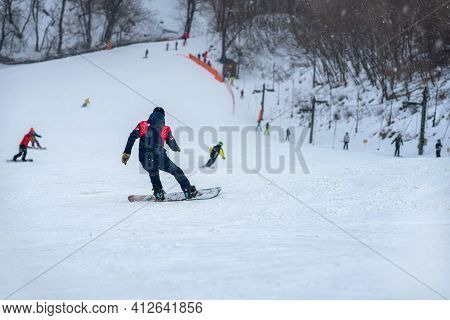 Down Slope On Snow Covered Mountain. Back View Of Snowboarder Riding On Slope, Blurred Selective Foc