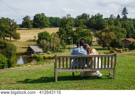 Newlyweds Sitting Close Together On The Wooden Bench. Bride And Groom Embrace Each Other In The Park