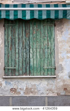 Green wooden shutters over window - Emilia Romagna