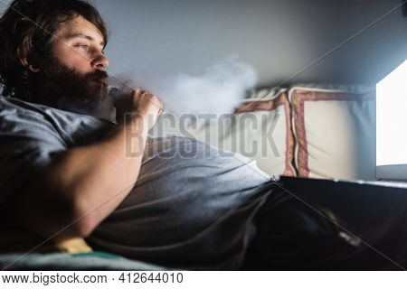 Overweight Bearded Man Vapes Lying On The Sofa While Watching A Movie On His Laptop. Lazy Person Vap
