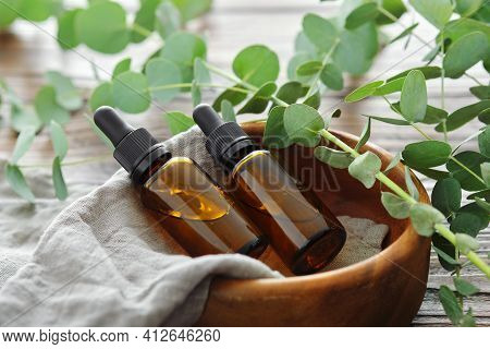 Two Bottles Of Eucalyptus Essential Oil In Wooden Bowl And Eucalyptus Twigs On Table. Alternative Me
